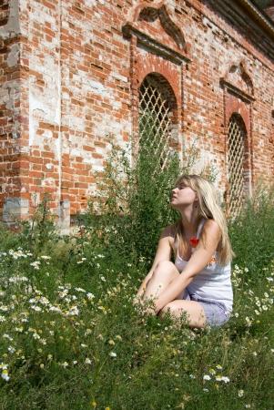A gyönyörű lány ül a partján, egy napsütéses napon Stock fotó