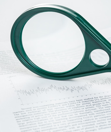 Magnifier on article with the schedule, studio shot