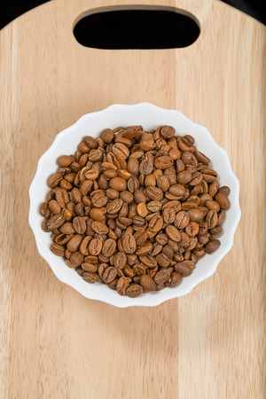 Coffee beans in a cup wooden board, studio shot