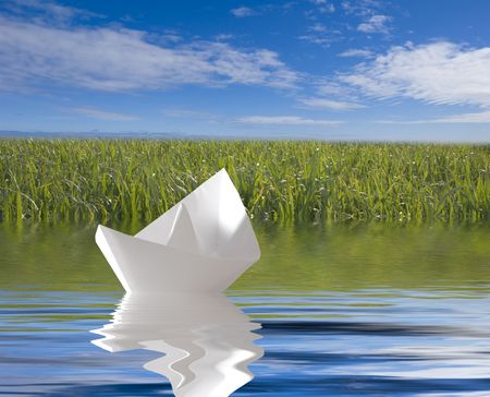paper ship in blue like near green coast Stock Photo