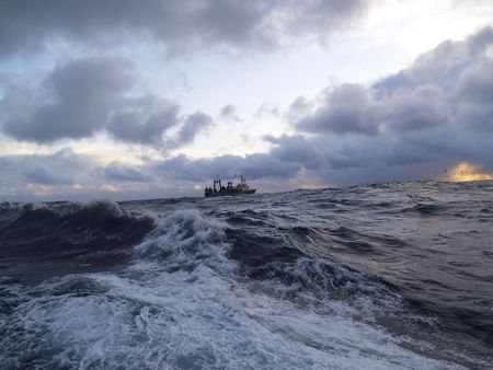 Trade vessel at ocean in storm conditions photo