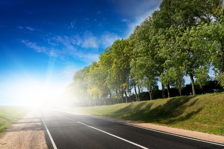 Tardy Sonnenuntergang über ländliche Straße zum grünen Hügeln.  Belarus Standard-Bild