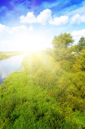 as far as the eye can see: Scenery. Blue river, cloud sky, green shores as far as the eye can see.  Stock Photo