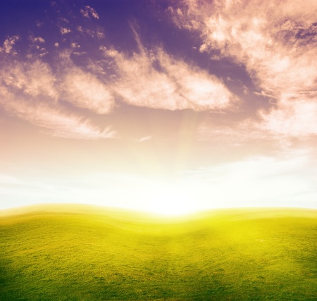 Green grass hills under colour cloud sky. Sunset scene. photo
