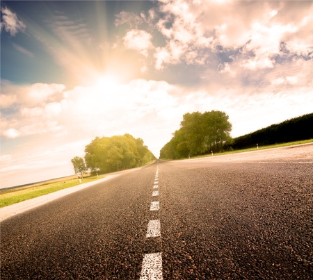 car on road: Asphalt road in green meadow  Belarus  Golden sunset