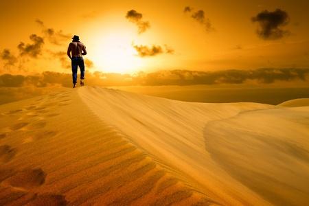 weariness: El hombre estar� listo a caer de cansancio en el desierto Puesta de sol de oro del desierto