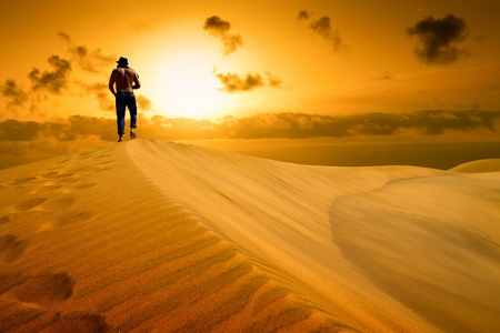 weariness: The man be ready to drop with weariness in desert  Sunset gold desert  Stock Photo