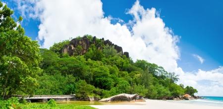 brige: Mahe island, Seychelles. Sunny Beach. Black rock in green forest.