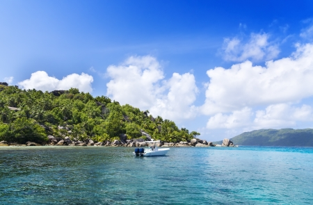 White yacht near sandy coast of seychelles. Sunny green island. photo