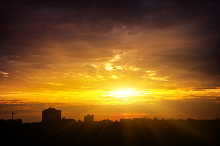 Colorful sunset in the city. The silhouettes of the buildings. The suns rays at sunset. photo