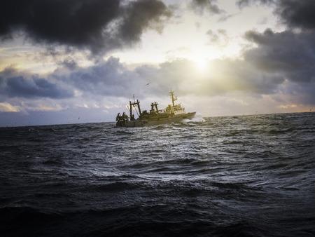 fishing ship: Fishing ship in strong storm. Sunrise.