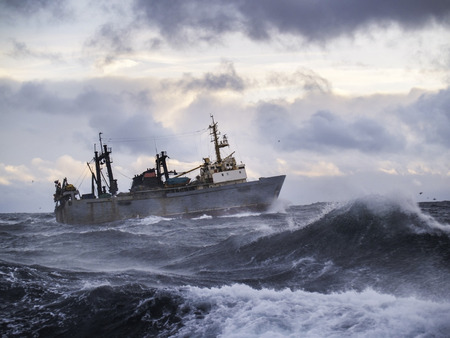 storm sea: Fishing ship in strong storm. Sunrise.