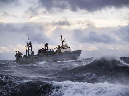 fishing scene: Fishing ship in strong storm. Sunrise.