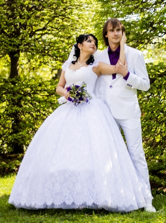 Elegant bride and groom posing together outdoors on a wedding day photo