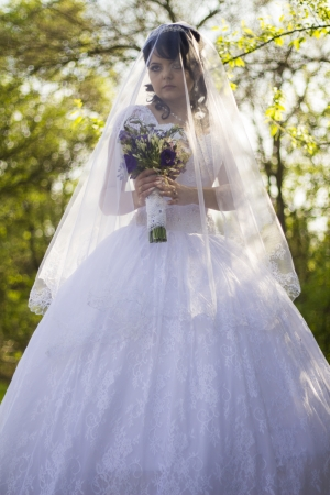 The bride is closed veil with a bouquet in hand photo