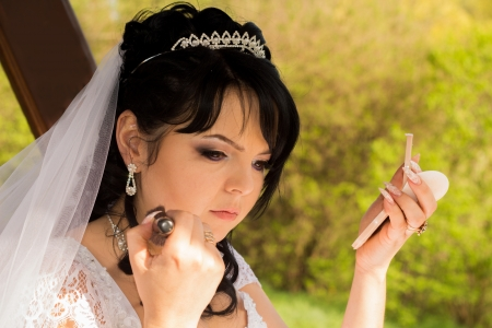 herself: young bride is doing makeup Stock Photo