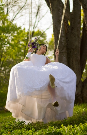 Portrait of a beautiful bride in white wedding dress sitting on swing outdoors photo