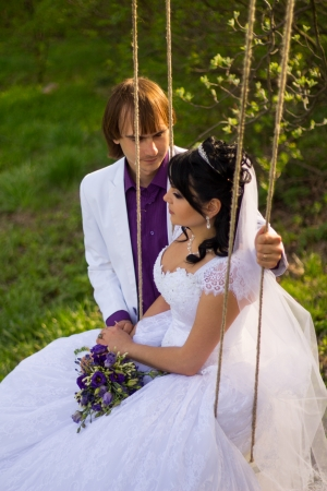 bride and groom swinging on a swing photo
