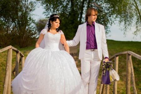 Happy just married couple standing on the small bridge photo
