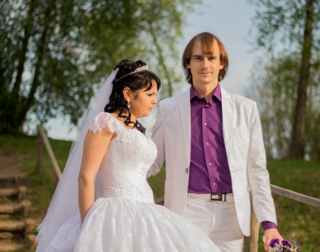latvia girls: Happy just married couple standing on the small bridge