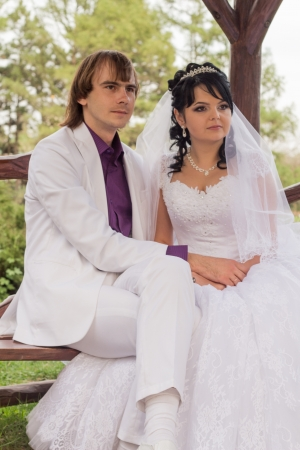 Couple in love bride and groom posing sitting on wooden bench in gazebo in their wedding day in summer. photo