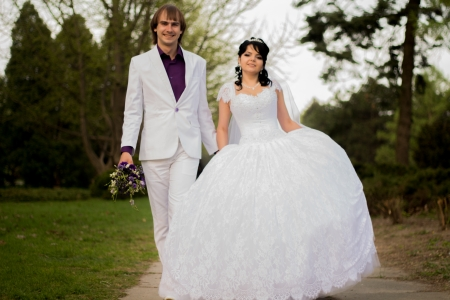 Happy bride and groom in shady alley on wedding walk photo