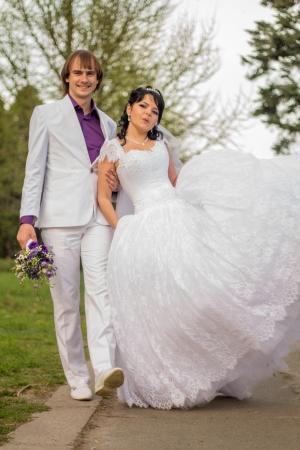 shady: Happy bride and groom in shady alley on wedding walk