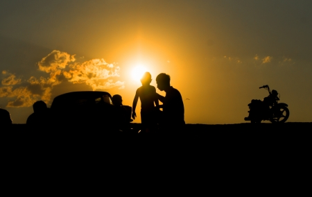 Silhouettes of father and child and Motorcycle  against the sunset photo