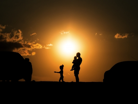 happy family of three people,celebrate outside at Sunset, Silhouette against the evening sky photo