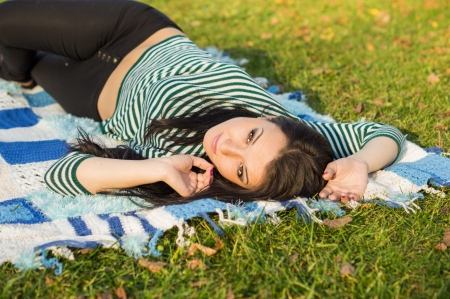 young woman laying down on the ground in autumn park photo