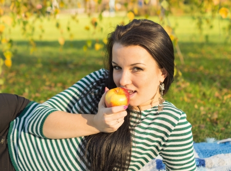 Autumn woman happy smiling outdoors, beautiful Woman holding autumn apples and fruits. Portrait of young woman walking outdoors at fall. Attractive woman walking in autumn park. photo