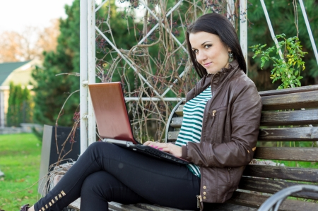 Young beautiful brunette student in profile sits on bench about university and works behind laptop. photo
