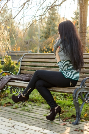 girl sitting on bench outdoors photo