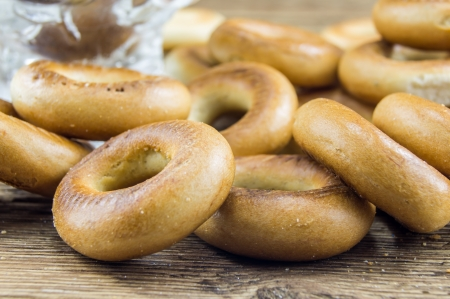 boublik: Closeup of a group of assorted bagels on a wood table top with burlap in the background