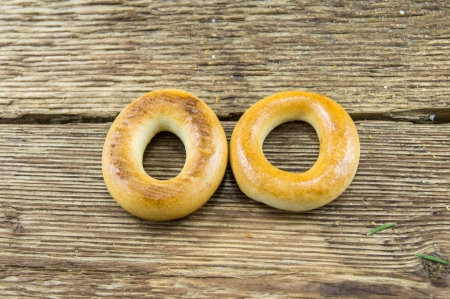 baranka: Closeup of a group of assorted bagels on a wood table top with burlap in the background