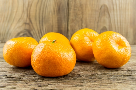 Ripe tangerines on wooden background photo