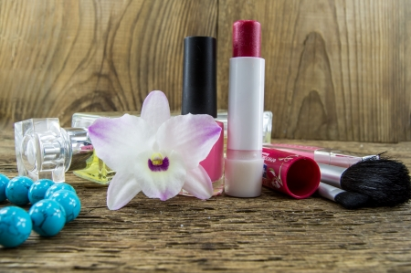 cosmetics and flowers on table on wooden background photo