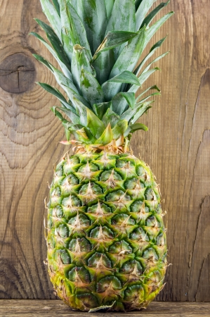 Pineapples on wooden grunge background photo