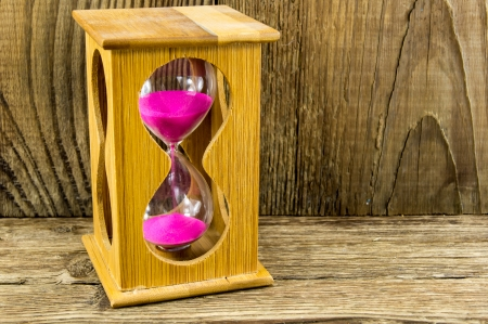 Hourglass with space for text on the wooden background photo