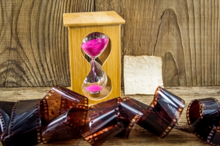 Hourglass and 35mm film with space for text on the wooden background photo