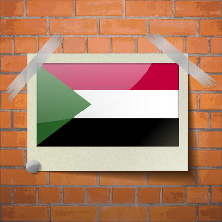 correctly: Flags of Sudan scotch taped to a red brick wall. Vector