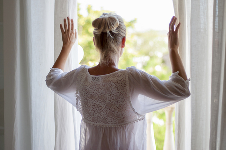 Newly lifted woman looking out the window in pijama. Foto de archivo