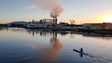 Canoeist paddling in a river at sunset, with a factory in the background blowing smoke.