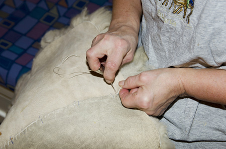 pices: Women stitch up two pices of white fleece