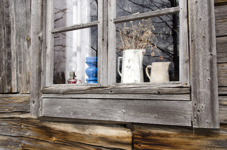 sommer: Window in a old timbered house with some sommer flowers left on inside, photo taken in the North of Sweden Stock Photo