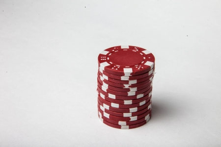 Red poker chips isolated on white Фото со стока