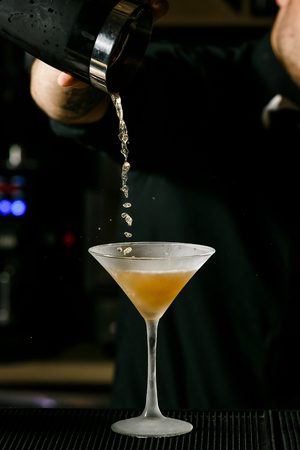 adding: Young handsome Barman in bar interior mixing alcohol cocktail. Professional bartender at work