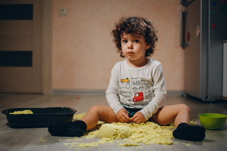 little boy playing with yellow kinetic sand on the floor at home