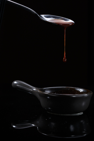 Melted milky brown chocolate pouring from a spoon, isolated on black.