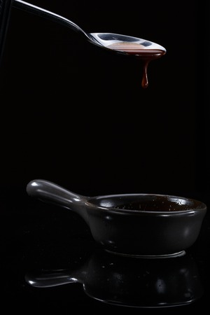 Melted milky brown chocolate pouring from a spoon, isolated on black